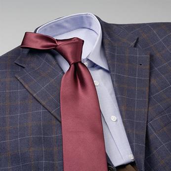 Estampado con liso Chaqueta azul a cuadros grandes con camisa en celeste y una corbata monocolor en rojo oscuro.